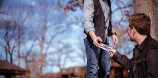 Ein Mann übergibt einem anderen Mann ein Ticket, Letzterer sitzt vor einem Baum