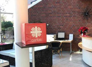 Auf einem Stehtisch liegt ein roter Quader, circa 50 mal 50 Zentimeter. mit aufgedrucktem Caritas-Logo.