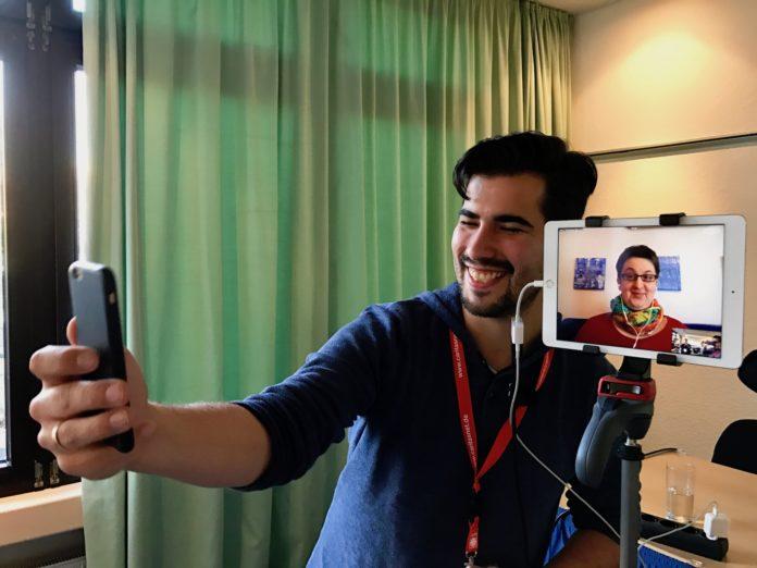 Ein Mann hält ein Mann auf Gesichtshöhe, neben ihn auf einem iPad auf einem Stativ eine Frau. Der Mann macht von sich und der Frau ein Selfie.