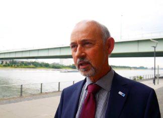 Ein älterer Mann mit Bart um den Mund im Anzug, steht vor der Südbrücke in Köln