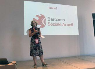Eine Frau mit Mikrofon steht auf der Bühne.