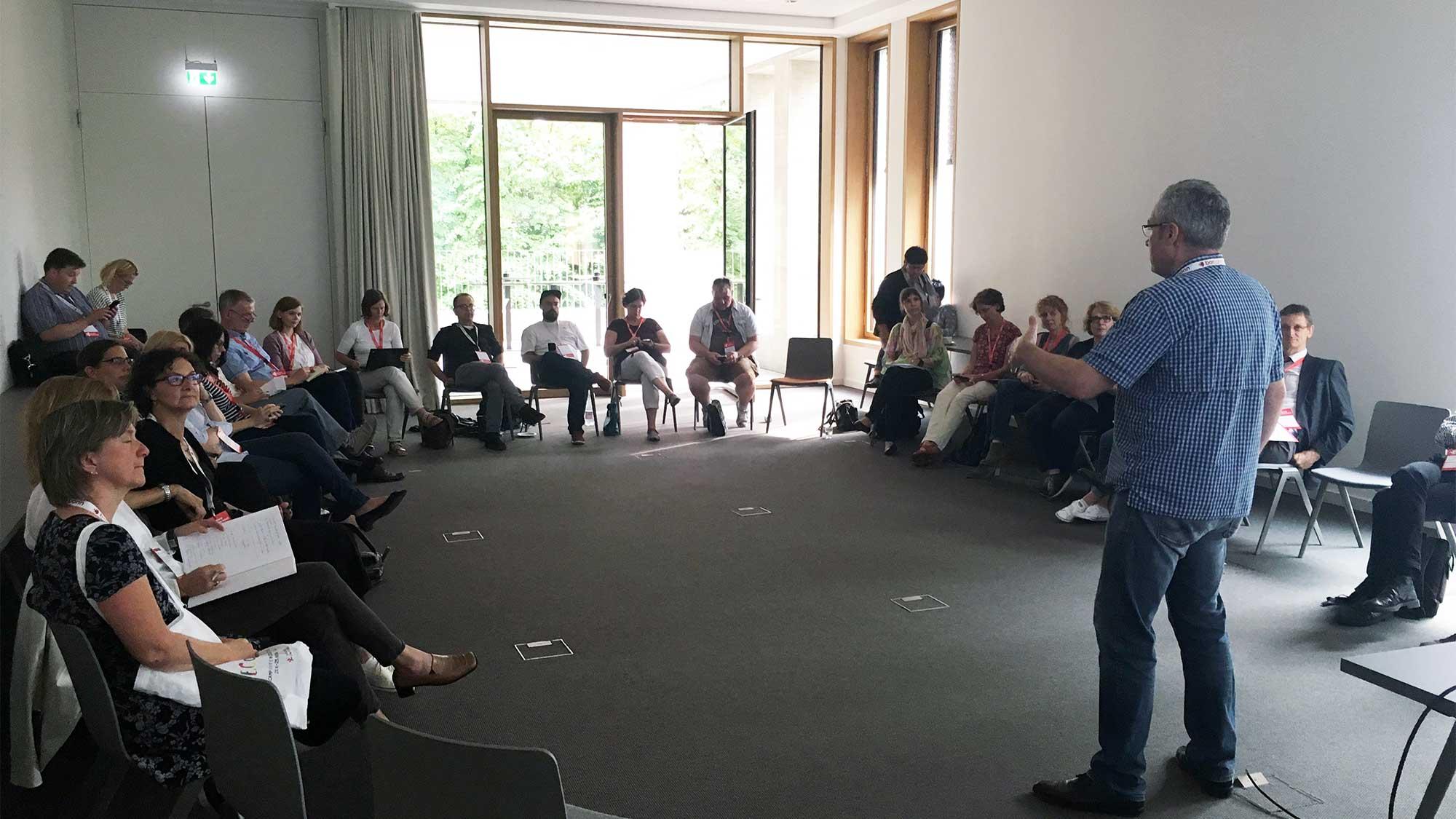 Ein Mann hält einen Vortrag, im Dreiviertelkreis vor ihm etwa dreißig Menschen.
