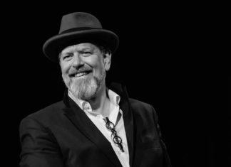 Ein Mann mit grauem Bart und Hut lächelt in die Kamera.