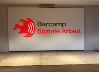 Eine leere Bühne mit großer Leinwand, auf die das Logo des Barcamp Soziale Arbeit montiert wurde.