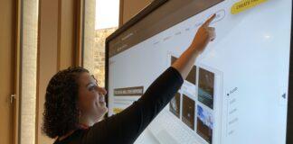 Eine Frau steht vor einem großen Monitor und drückt auf eine Schaltfläche.