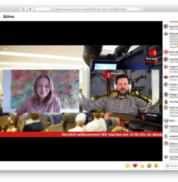 Screenshot aus der virtuellen Location. Links eine Menüleiste, rechts verpixelt ein Textchat, in der Mitte groß die beiden Moderator/innen Inga und Johannes.